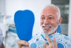 Smiling senior man checking teeth