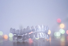 Invisalign clear aligners in front of backdrop.