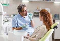 Dentist talking to woman about tooth replacement options