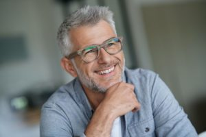 smiling gray-haired man happy about the cosmetic benefits of dental implants