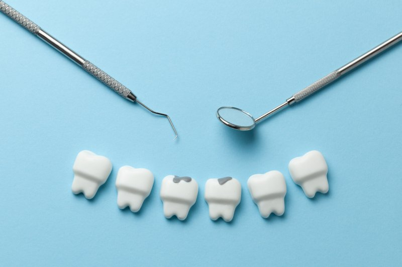 teeth with cavities and dental tools