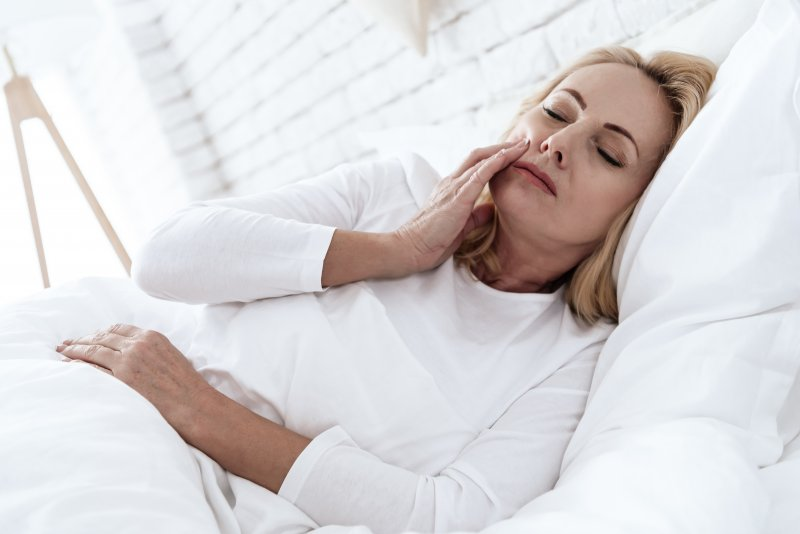 woman with toothache while in bed