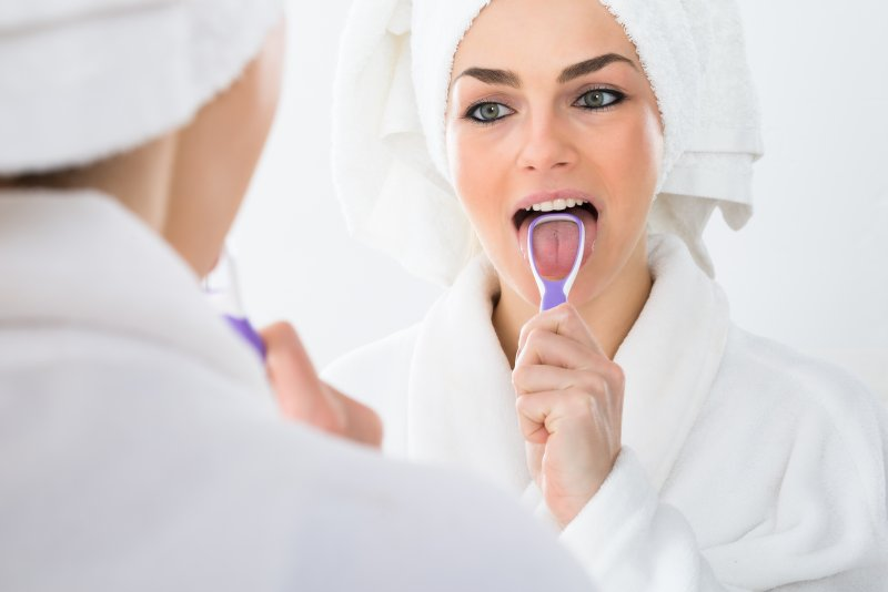 woman cleaning her tongue with tongue scraper
